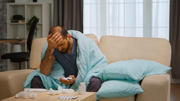 Smutny i chory człowiek na kanapie owinięty kocem podczas globalnej pandemii.