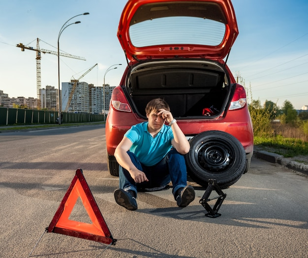 Smutny i przygnębiony mężczyzna siedzący obok samochodu z przebitą oponą