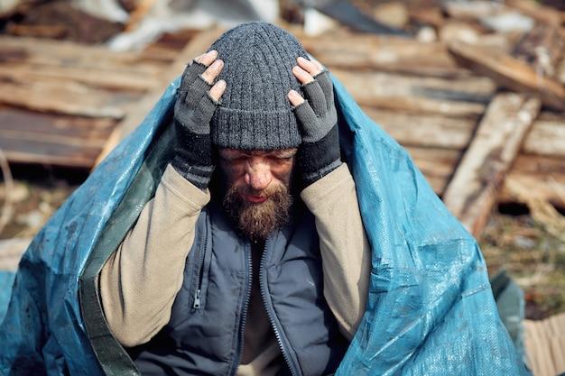 Smutny i zdenerwowany bezdomny i bezrobotny mężczyzna w ruinach