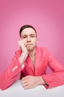 Smutny lub znudzony młody człowiek w czerwonej glamour kurtce na tułowiu siedzi przy biurku i patrzy na ciebie w izolacji