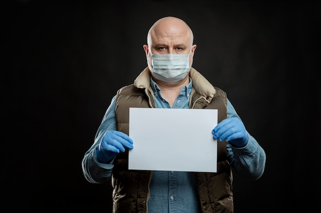 Smutny łysy mężczyzna w medycznej masce i rękawiczkach z pustym znakiem w dłoniach. miejsce na tekst. bezrobocie i globalny kryzys podczas pandemii koronawirusa.