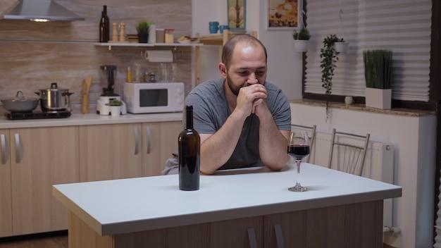 Smutny mąż pije czerwone wino, siedząc w kuchni. nieszczęśliwa osoba cierpiąca na migrenę, depresję, choroby i stany lękowe, wycieńczona z objawami zawrotów głowy, mająca problemy z alkoholizmem.