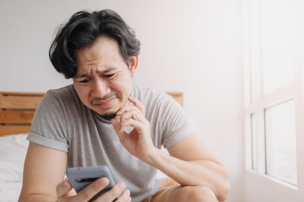 Smutny mężczyzna ma złe wiadomości na czacie online i czuje się rozczarowany na smartfonie