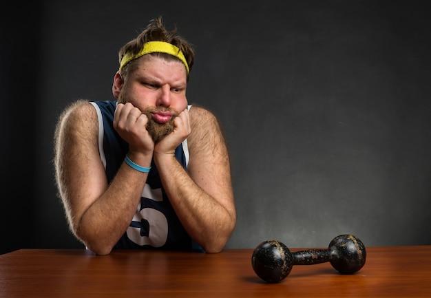 Smutny mężczyzna patrzący na hantle przy stole