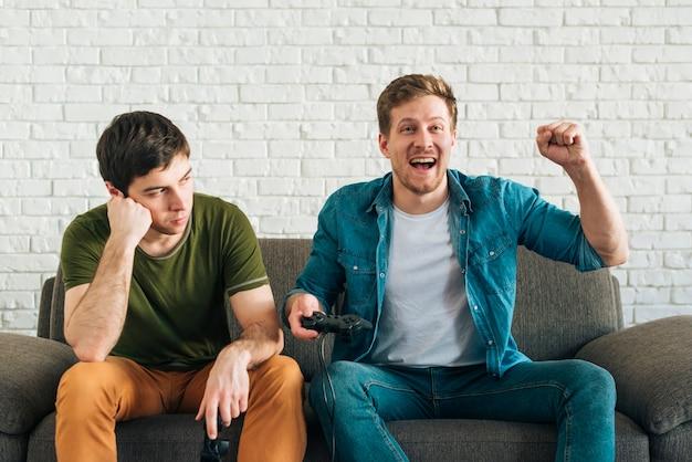 Smutny mężczyzna patrzeje szczęśliwego przyjaciela rozwesela po wygrywać grę wideo