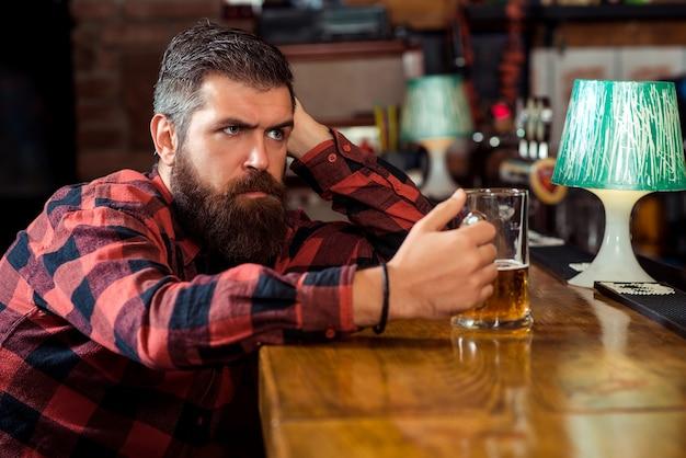 Smutny mężczyzna pije piwo w pubie. samotny brodaty mężczyzna przy barze