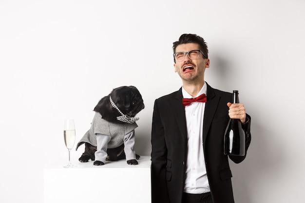 Smutny mężczyzna płacze i pije szampana z butelki, podczas gdy mops w uroczym stroju imprezowym gapi się zdezorientowany, stojąc na białym.