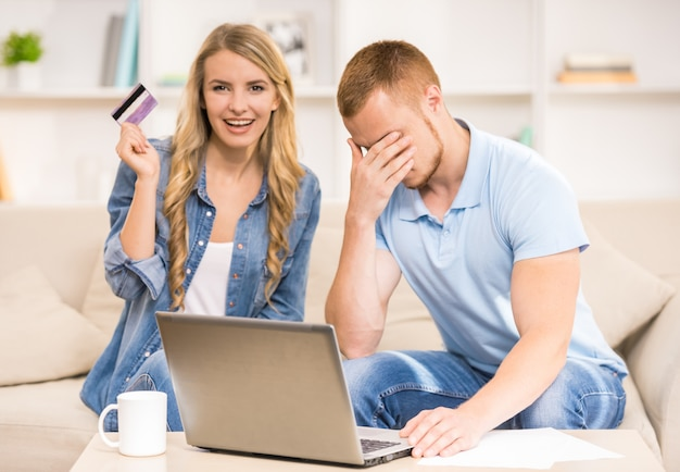 Smutny mężczyzna pracuje z laptopem podczas gdy żona trzyma kredytową kartę.