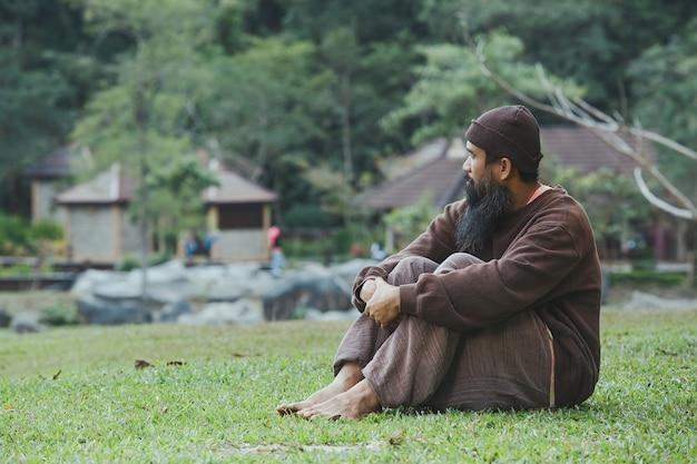 Smutny mężczyzna siedzący na zielonej trawie