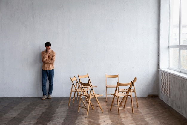 Smutny mężczyzna siedzący pod ścianą na sesji terapii grupowej