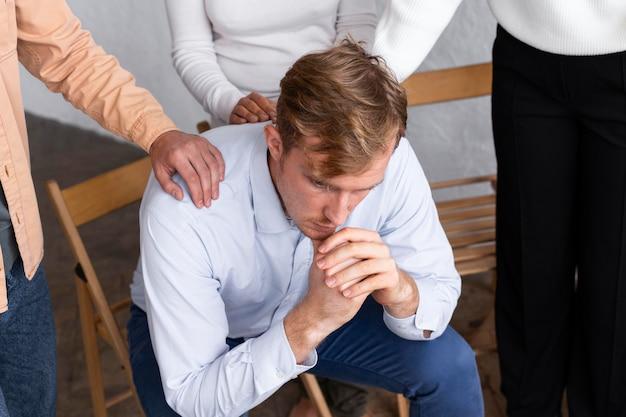 Smutny mężczyzna siedzi na krześle podczas sesji terapii grupowej