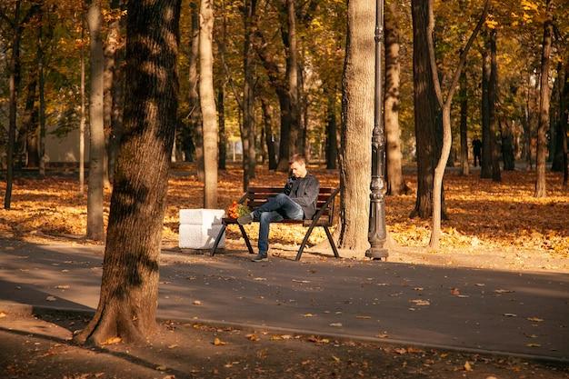 Smutny mężczyzna siedzi na ławce w jesiennym parku miejskim z bukietem kwiatów i czeka długo z niezadowolonym wyrazem twarzy. nieudana data