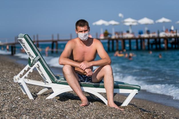 Smutny mężczyzna siedzi na leżaku w masce samotnie na plaży podczas epidemii grypy covid 19