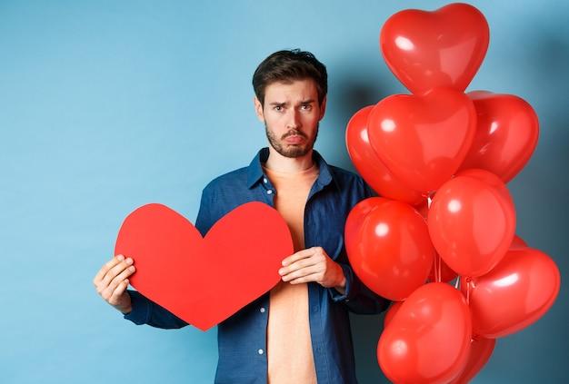 Smutny mężczyzna szuka załamanego serca i samotny, trzymając papierowe czerwone serce i stojąc w pobliżu balonów na niebieskim tle.