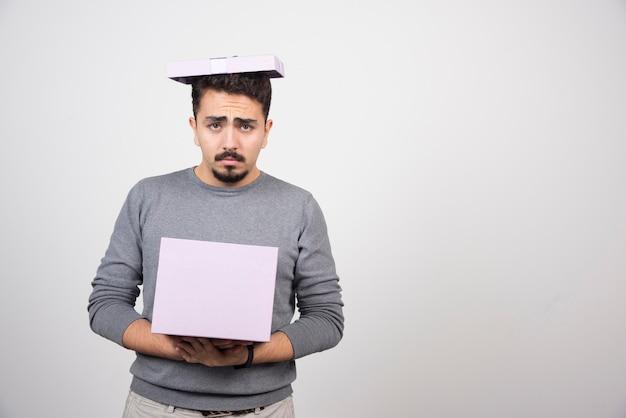 Smutny mężczyzna trzyma w rękach fioletowe pudełko.