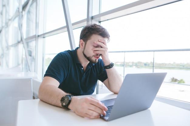 Smutny mężczyzna w przypadkowych ubraniach siedzi przy stole i zamyka dłonią twarz.