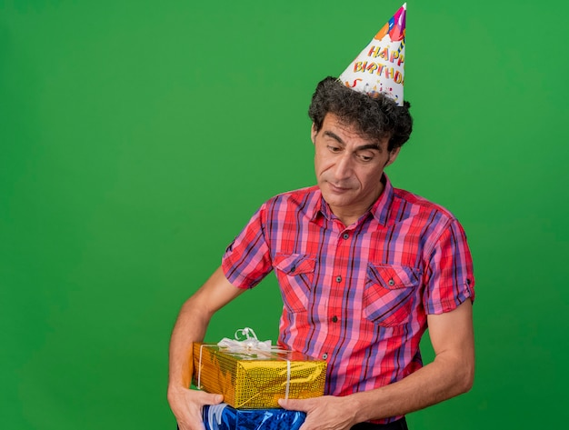 Smutny mężczyzna w średnim wieku kaukaski party czapkę urodzinową, trzymając paczki prezentów patrząc w dół na białym tle na zielonym tle z miejsca na kopię