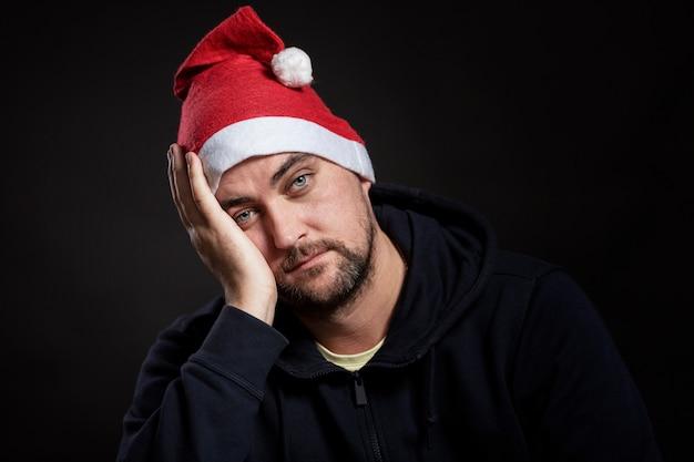 Smutny mężczyzna z czerwoną brodą w czapce mikołaja zakrył twarz dłonią.
