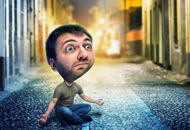 Smutny mężczyzna z dużą głową siedzący na ulicy w nocy