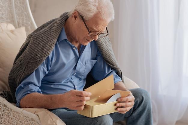 Smutny miły starszy pan przewracający swoje stare listy i wspominający swoją młodość będąc sam