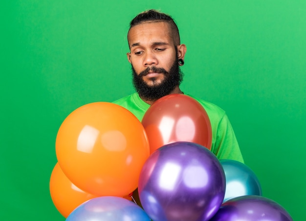 Smutny młody afroamerykański facet w zielonej koszulce stojący za balonami odizolowanymi na zielonej ścianie