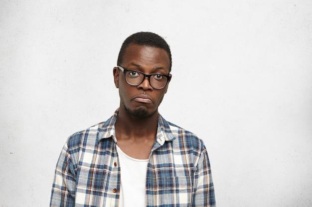 Smutny młody afroamerykański mężczyzna w modnej koszuli i okularach wykrzywia usta, czując się rozczarowany i nieszczęśliwy z powodu swojego życia, stojąc w izolacji