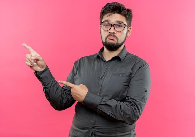 Smutny młody biznesmen noszenie okularów punktów z boku na białym tle na różowo z miejsca na kopię