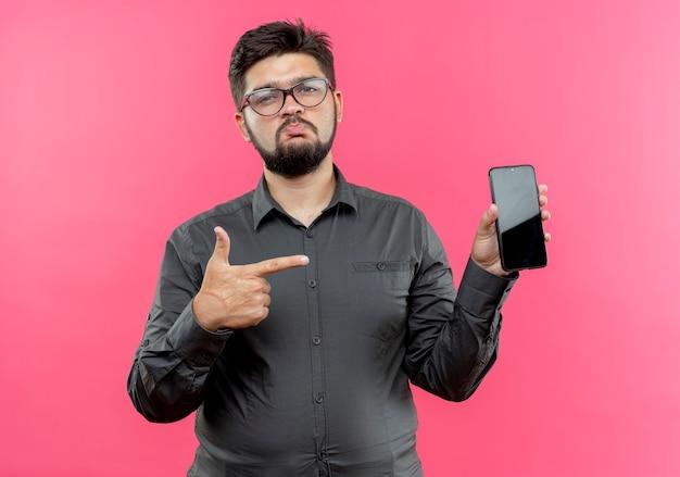 Smutny młody biznesmen w okularach gospodarstwa i wskazuje na telefon na różowym tle