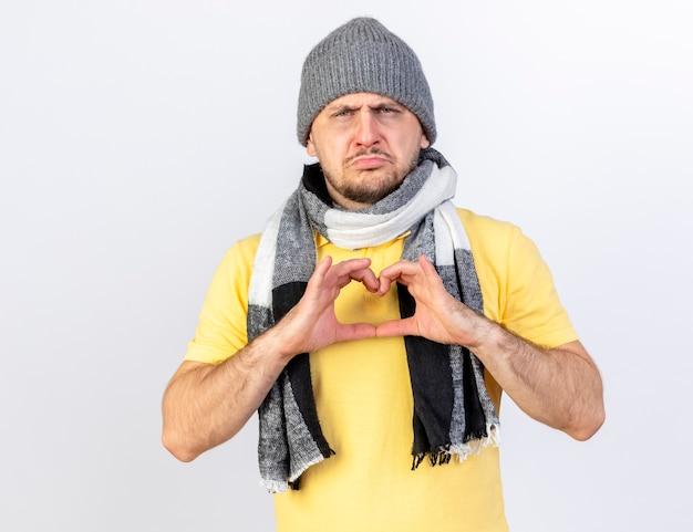 Smutny młody blondyn chory ubrany w czapkę zimową i szalik gesty serca znak na białym tle na białej ścianie