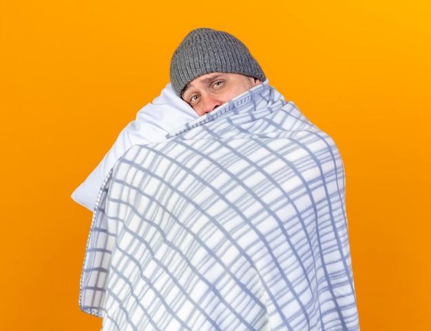 Smutny młody blondyn chory ubrany w czapkę zimową zawinięty w kratę trzyma i kładzie głowę na poduszce na pomarańczowej ścianie