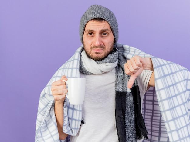 Smutny młody chory czapka zimowa z szalikiem, trzymając kubek herbaty, pokazując kciuk w dół na białym tle na fioletowo