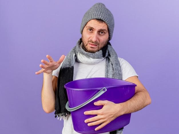 Smutny młody chory czapka zimowa z szalikiem, trzymając plastikowe wiadro na fioletowym tle