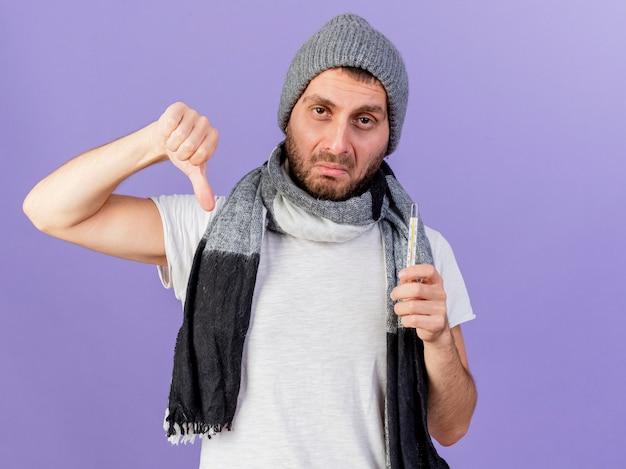 Smutny młody chory czapka zimowa z szalikiem, trzymając termometr i pokazując kciuk w dół na białym tle na fioletowo