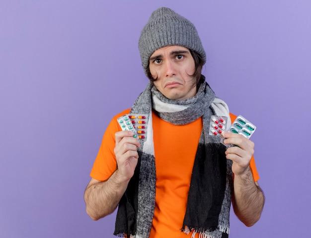 Smutny młody chory człowiek ubrany w czapkę zimową z szalikiem trzymając pigułki na fioletowym tle
