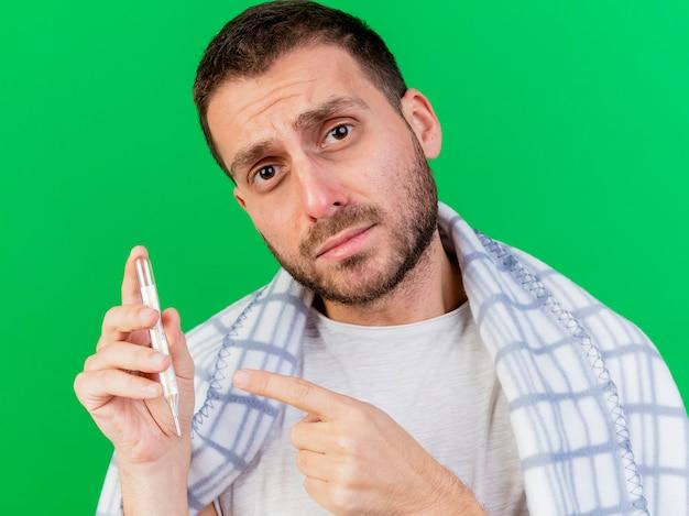 Smutny młody chory człowiek zawinięty w kratę gospodarstwa i wskazuje na termometr na zielono