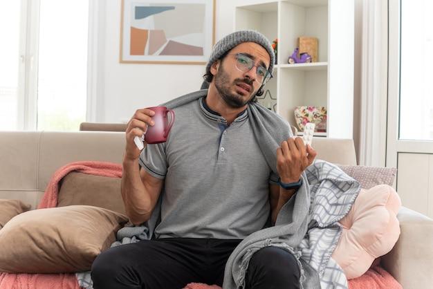 Smutny młody chory kaukaski mężczyzna w okularach optycznych owinięty w kratę w czapce zimowej, trzymając kubek i opakowanie blistrowe leku, siedząc na kanapie w salonie