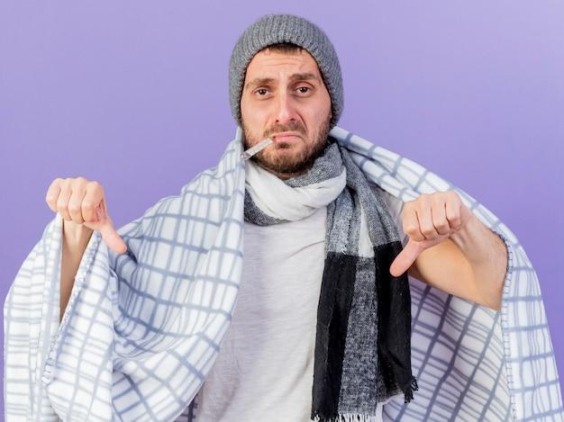 Smutny młody chory mężczyzna w czapce zimowej z szalikiem wkłada termometr do ust owinięty w kratę i pokazuje kciuki w dół odizolowane na fioletowo