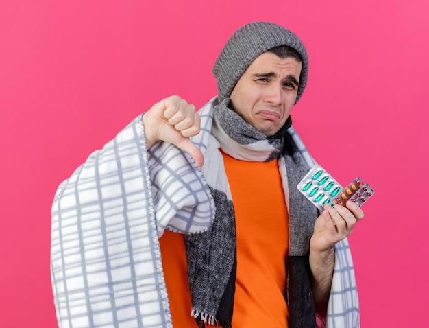 Smutny młody chory w czapce zimowej z szalikiem owiniętym w kratę trzymając pigułki i pokazując kciuk w dół na różowym tle