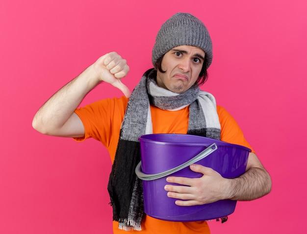 Smutny młody chory w czapce zimowej z szalikiem trzyma plastikowe wiadro pokazując kciuk w dół na różowym tle