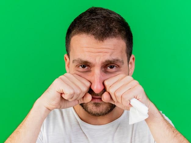 Smutny młody chory wycierając oczy pięściami na zielono