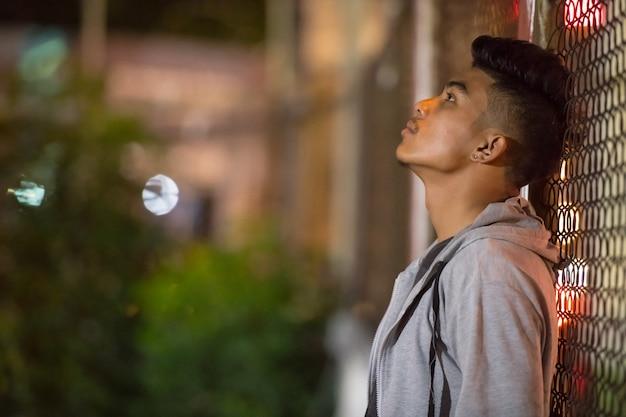 Smutny młody człowiek azji, opierając się na płocie na ulicy miasta w nocy