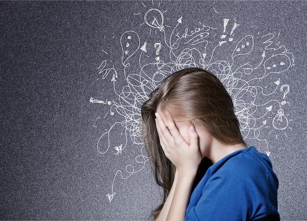 Smutny młody człowiek o zmartwionej, zestresowanej twarzy i mózgu roztapiającym się w linie znaków zapytania.