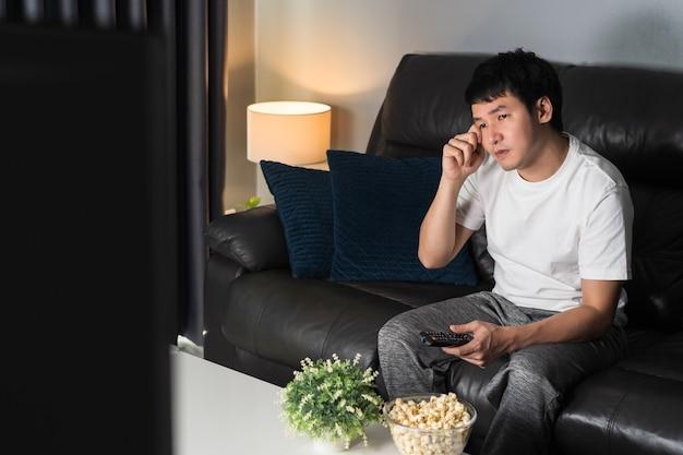 Smutny młody człowiek ogląda telewizję i płacze na kanapie w nocy