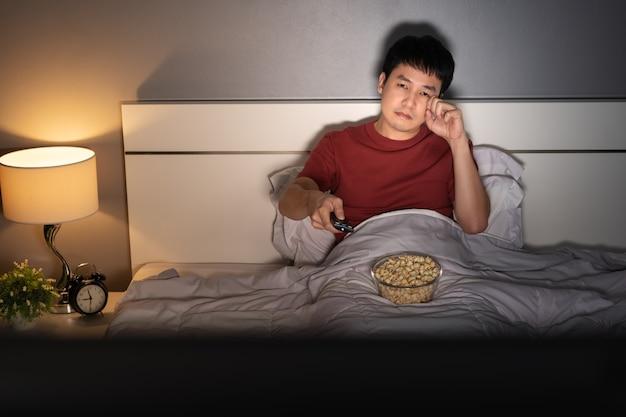 Smutny młody człowiek ogląda telewizję i płacze na łóżku w nocy (film romantyczny)