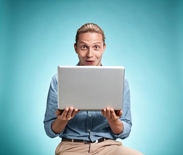 Smutny młody człowiek pracuje na laptopie