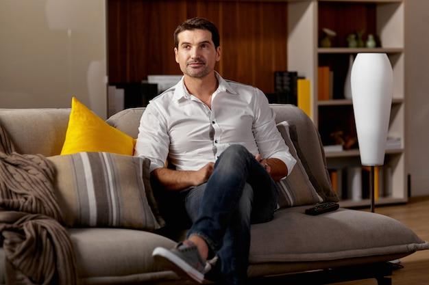 Smutny młody człowiek relaksujący na wygodnej kanapie z pilotem do telewizora. widok poziomy.