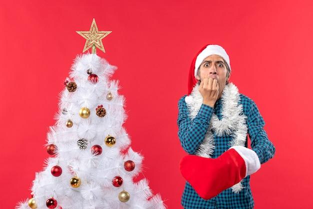 Smutny młody człowiek w kapeluszu świętego mikołaja w niebieskiej koszuli w paski i noszący swoją świąteczną skarpetę