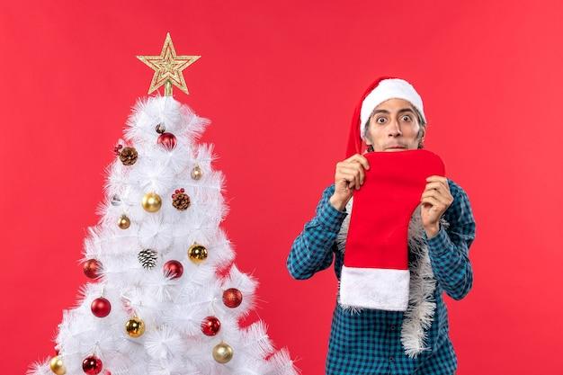 Smutny młody człowiek w kapeluszu świętego mikołaja w niebieskiej koszuli w paski i pokazujący swoją świąteczną skarpetę