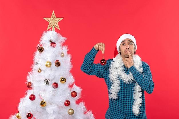 Smutny młody człowiek w kapeluszu świętego mikołaja w niebieskiej koszuli w paski i trzymając dodatek do dekoracji
