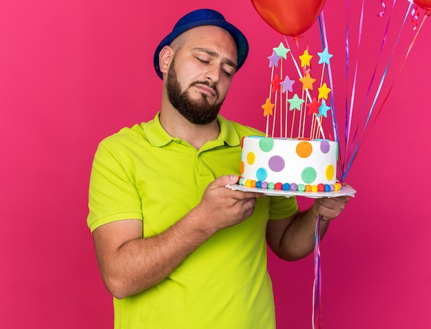 Smutny młody człowiek w niebieskiej imprezowej czapce, trzymający balony i patrzący na ciasto w dłoni